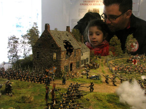 Family viewing the Battle of Brooklyn diorama at OSH