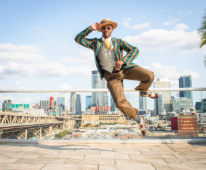 Musician Dandy Wellington posting in front of the NYC skyline