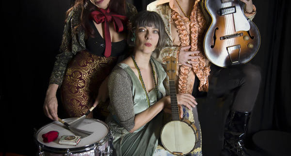 The Vicki Kristina Barcelona Band grouped with their instruments in front of a black background