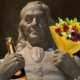 A statue of Benjamin Franklin holds a bouquet of flowers and a bottle of champagne