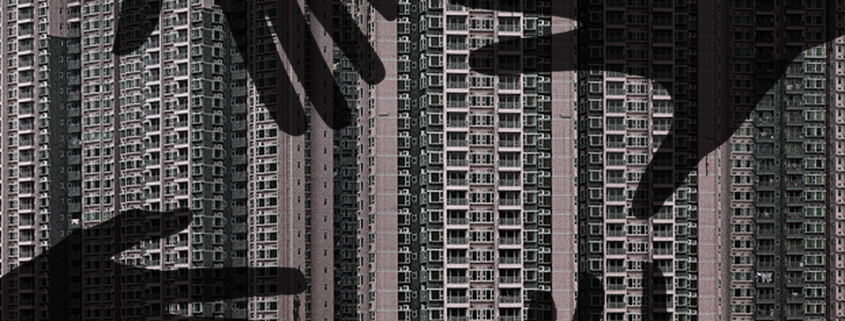 Shadows of four outstretched hands over grey apartment buildings
