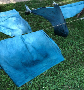blue dyed fabric drying on a clothesline over grass