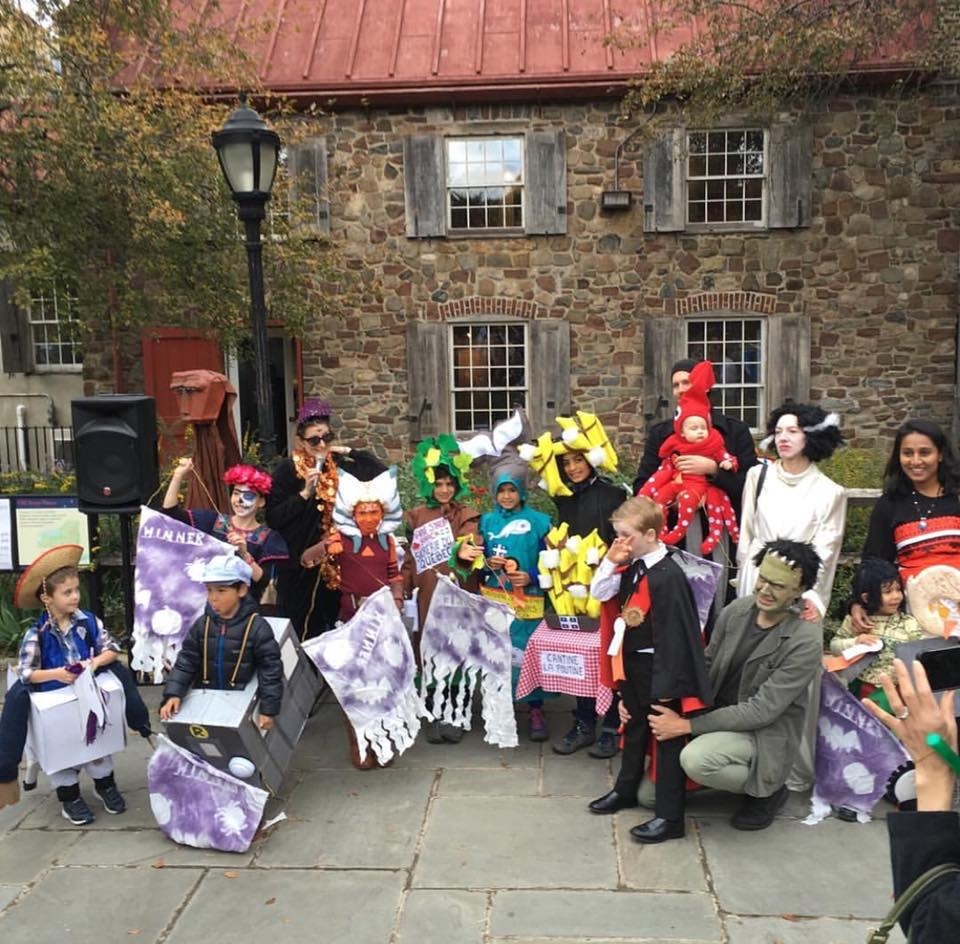 Children and adults dressed in halloween costumes pose in front of the Old Stone House