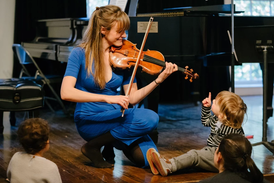 A woman kneels while playing violin for onlooking children