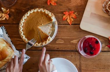 Pumpkin Pie being cut into slices on wooden table